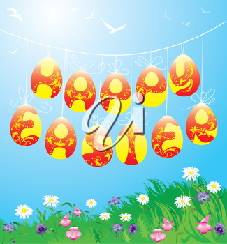 Hanging Easter eggs on spring blue sky background