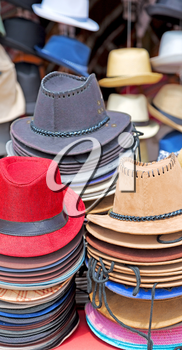 in a old market lots of colorated hats  like background clothes