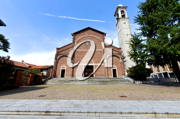 in  the cardano al campo old   church  closed brick tower sidewalk italy  lombardy