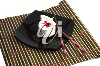 white cake in the form of a drop, on a black plate, with chopsticks