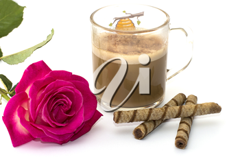 beautiful rose and cappuccino in the transparent mug