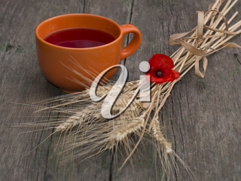 still life a clay mug with juice, wheat and a flower of poppy, a subject flowers and drinks
