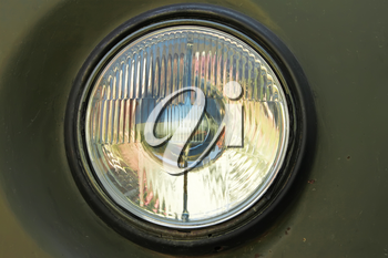 Old car round headlight against a dark green painted rusty body
