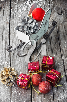 Christmas sleigh with pine cones and decorations on wooden background.