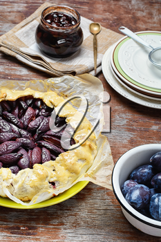 Rustic pie with plums and plum jam on wooden background