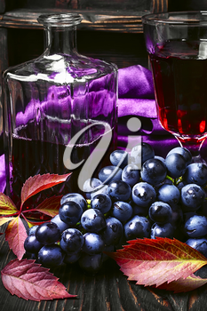 Young red wine in the glass from the autumn harvest of grapes.Dark key