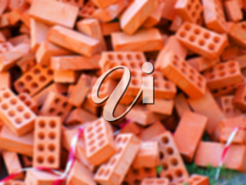 Defocused and blur image of large pile of red bricks for the construction in a full disorder
