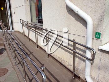 Ramp for physically challenged with metal railing at the entrance to an office building in sunny summer day