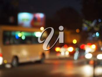 Abstract night scene with bus and headlights. Blur and defocused lights from the headlights of cars and traffic lights can be used as background.