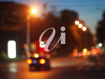 Defocused and blur of night scene - cars with headlights on driving on city road against the evening sky was blurred for use as a background