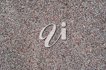 Top view of a background of small black, red and white stones on a flat surface across the image field