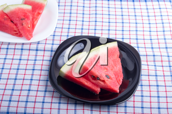 View from above on the pieces of juicy red watermelon on a black and white plate on a fabric tablecloth