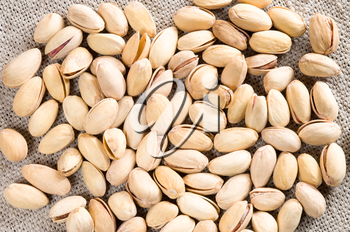 Top view of a lot of salty pistachios on a gray sacking