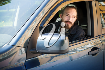 Bearded serious Asian man, driver of modern Japanese crossover suv car, outdoor portrait in open car window