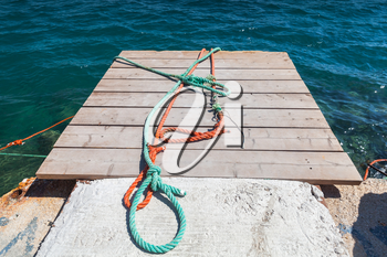 Colorful nautical ropes lay on small wooden pier. Zakynthos, Greece