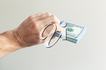 Bundle of One Hundred Dollars notes in hand over white wall background