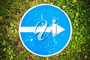 Right only, round blue road sign with white directional arrow lays on green grass