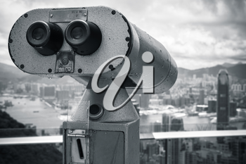 Monochrome photo of tourist binocular telescope for Hong Kong city observation from Victoria Peak viewpoint