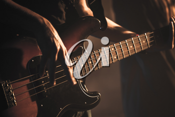 Guitarist plays on of bass guitar, soft selective focus, live music theme