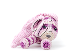 Knitted rabbit toy lays isolated on white background