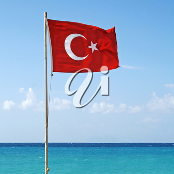 National flag of Turkey waving in the wind with Mediterranean sea and sky on the background