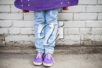 Teenager in blue jeans and gumshoes stands with skateboard near gray urban brick wall