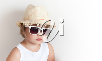 Cute Caucasian little girl in straw hat and sunglasses over white wall background