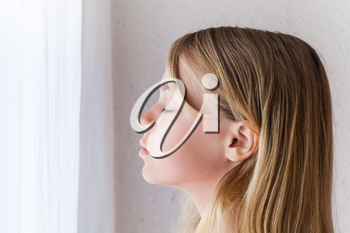 Closeup profile portrait of beautiful blond Caucasian girl with closed eyes near a window with white curtains