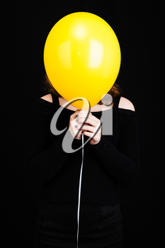 Girl hiding her face under yellow balloon, vertical studio shot over black background