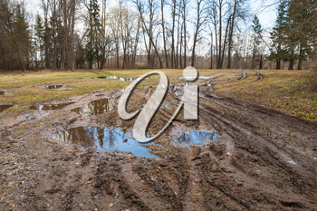 Dirty rural road with puddles and mud, springtime in Russian countryside