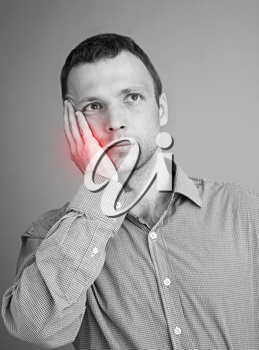 Young Caucasian man with toothache. Black and white stylized photo with red local ache spot