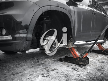 Replacing wheels on new black SUV car, two jacks hold the body in the raised position