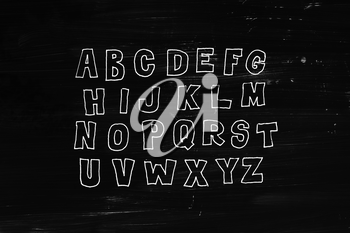 Hand drawn abc, doodle style. White letters over black chalkboard background, sketch illustration
