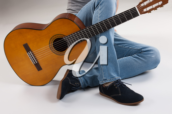 Man's legs and guitar on a studio background