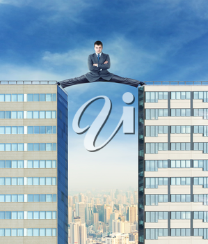 Businessman sits in the splits between two high buildings against the city