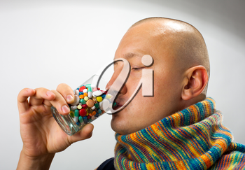 Ill man drinking cocktail of colorful pills