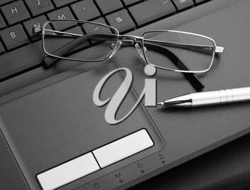 Businessman's glasses and pen on laptop computer