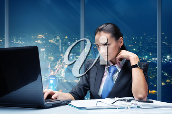 Businesswoman working in office against night cityscape