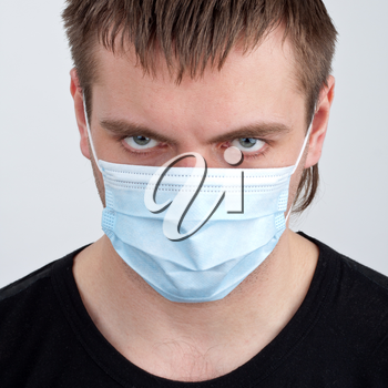 Portrait of pensive young man in medical mask