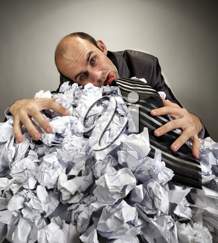 Exhausted depressive businessman laying on big heap of crumpled papers