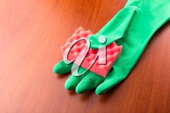 Cleaning glove with a red sponge on the table
