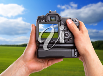 Hands holding digital camera and capturing rural landscape