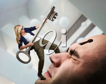 Young woman with key on the man's face with keyhole