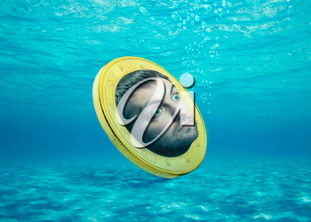 Coin with human face in the water