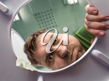 Man ready to puke in the bathroom in the toilet bowl