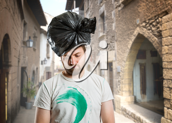 Sad man with trash pack on his head on the street