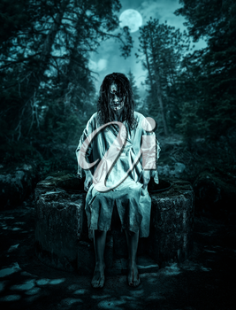 Scary corpse sitting on the well in the night forest. Halloween.