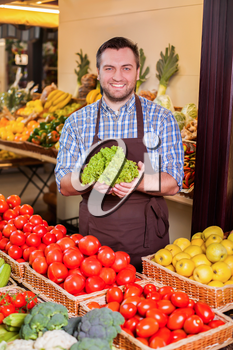 Smiling man offers fresh salad in in front of boxes with tomatoes and yellow apples. Grocery on the background.