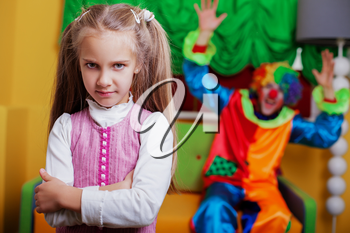 Upset little girl standing in the playroom.  Funny clown on the background.