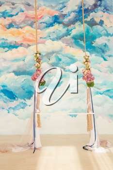 White wooden swing decorated with bouquets of flowers agaist abstract watercolor background. Romantic wedding concept.